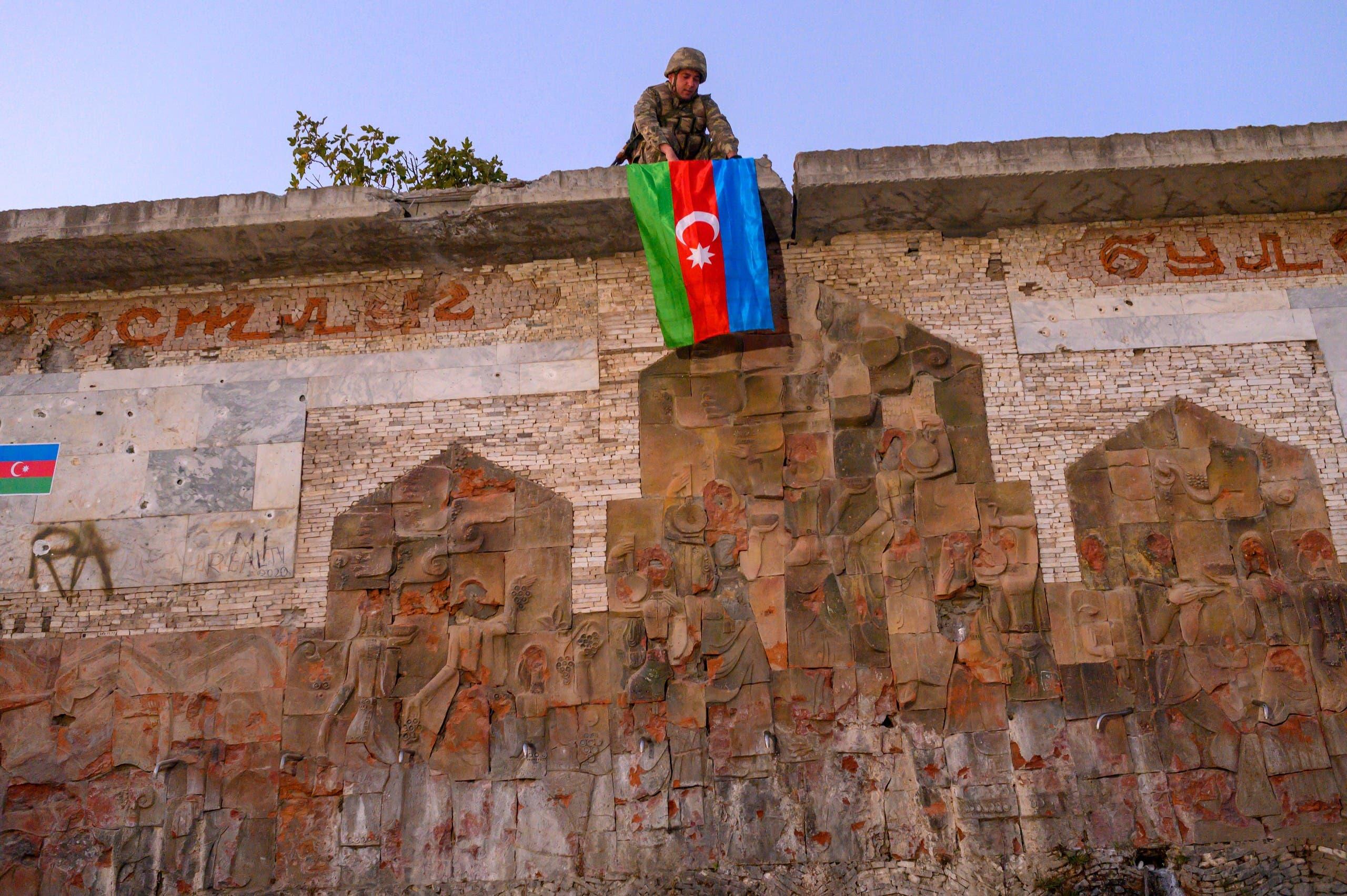 مقاتل أذربيجاني يسدل علم بلاده حدادا على القتلى