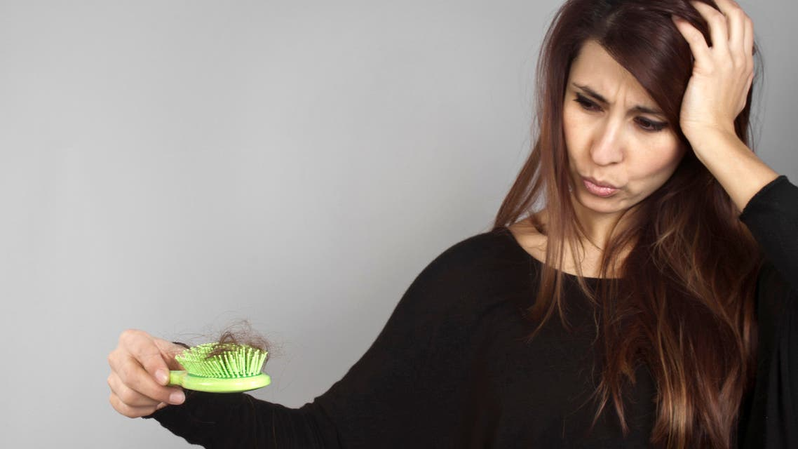 Balding problem women hand holding loss hair comb A long hair woman holding a green hairbrush full of hairs stock photo