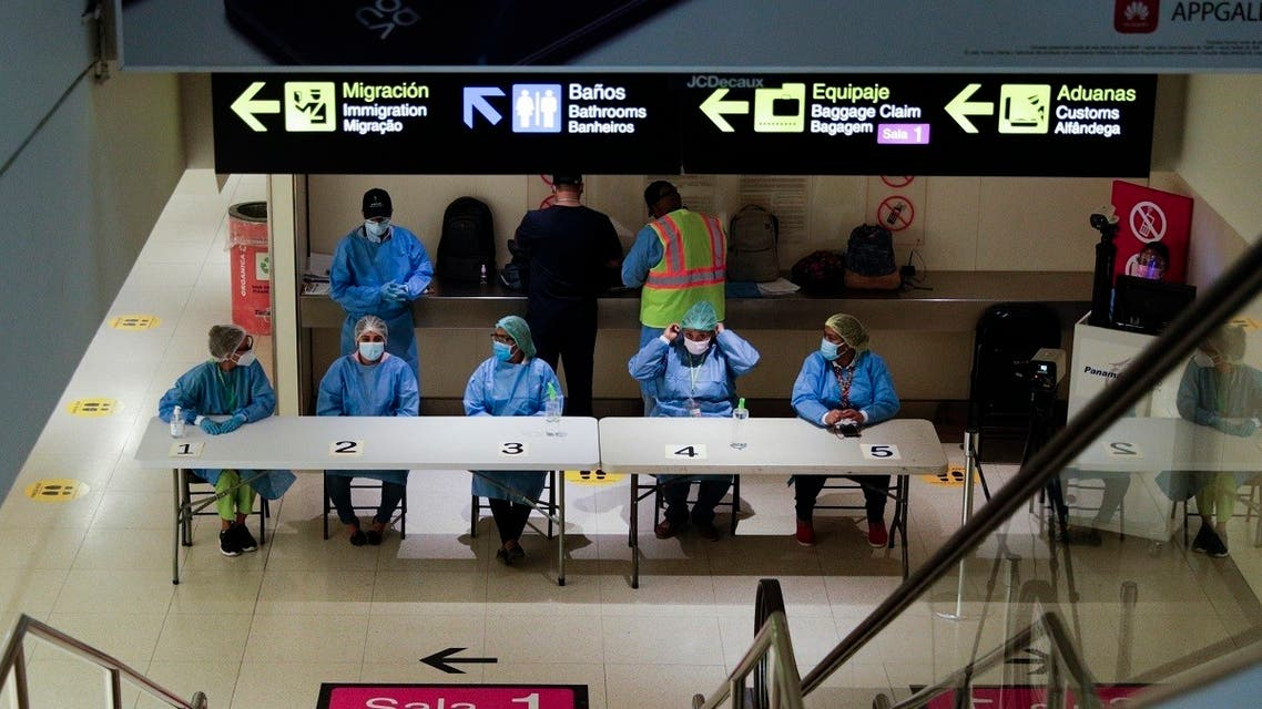Health workers wait to revise arriving passengers' COVID-19 test results and administer tests to those who do not have one to show at Tocumen International Airport in Panama City. (AP)