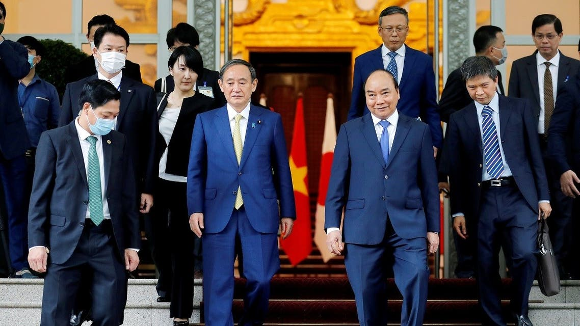 Japanese Prime Minister Yoshihide Suga and his Vietnamese counterpart Nguyen Xuan Phuc walk after a press briefing at the Government Office in Hanoi, Vietnam, October 19, 2020. (Reuters)