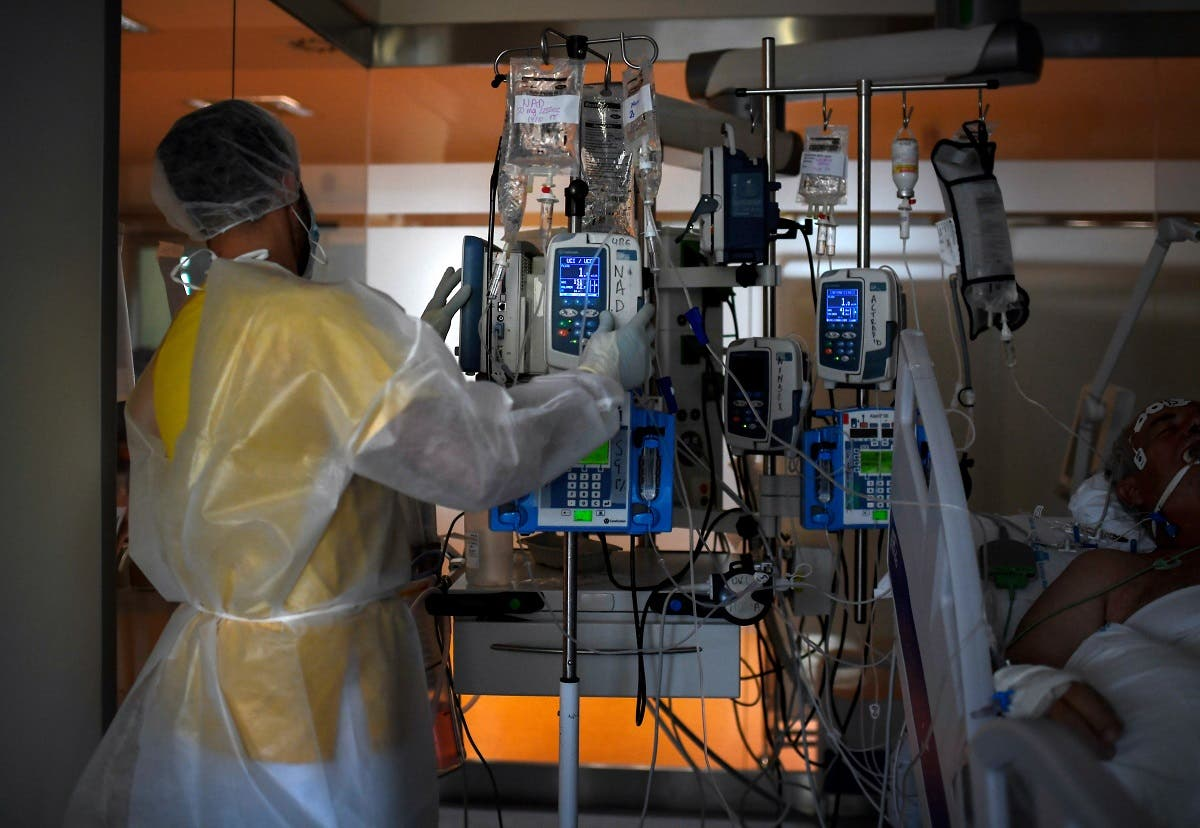 A healthcare worker in protective suit attends a COVID-19 patient at the Intensive Care Unit (ICU) of the Ramon y Cajal Hospital in Madrid on October 15, 2020. (AFP)