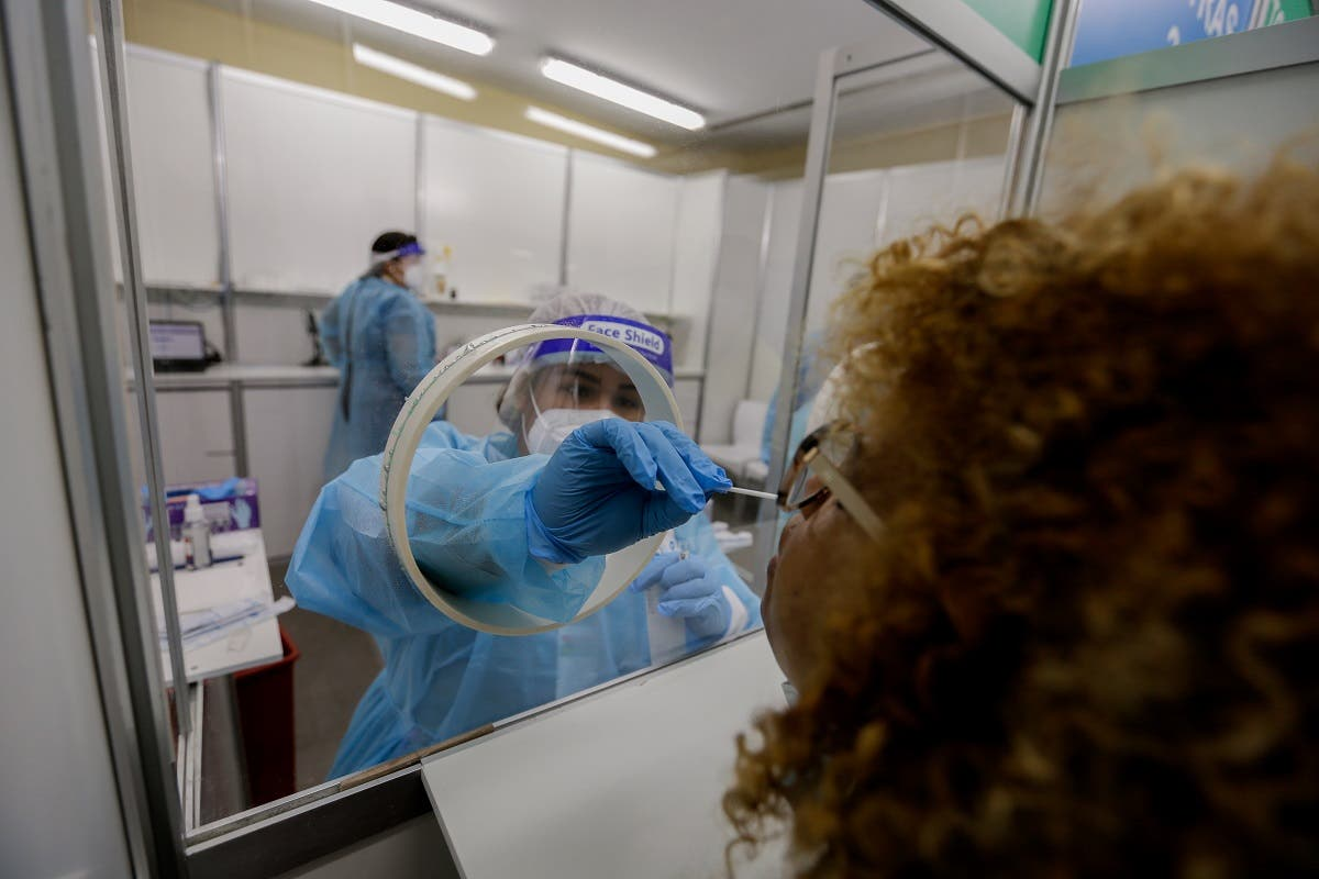 A health worker takes a swab sample from a woman at a rapid coronavirus testing station at Tocumen International Airport in Panama City on October 12, 2020. (AFP)