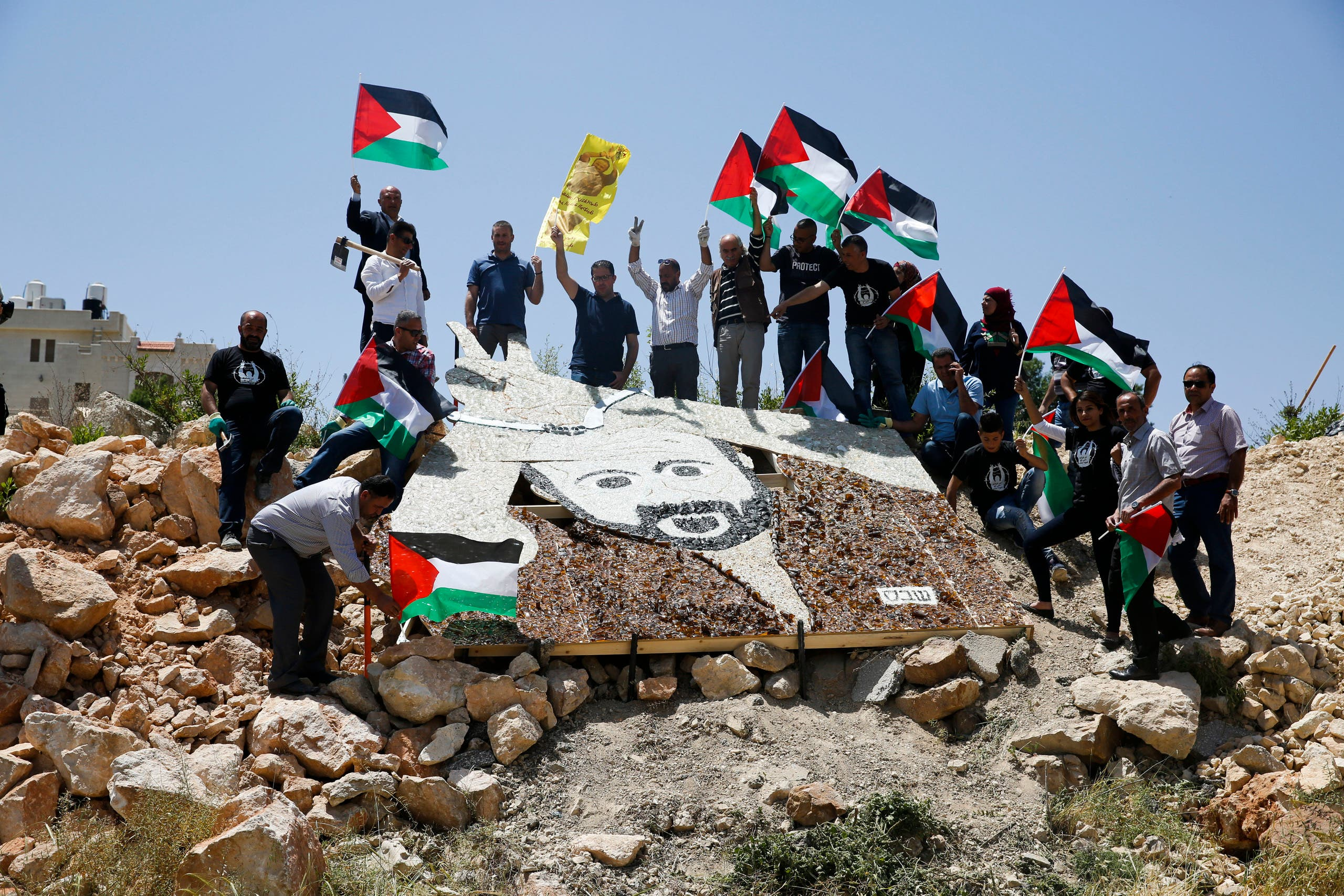 Palestinian activists stand around a mosaic portrait of Marwan Barghouti near an Israeli military installation in the West Bank city of Ramallah on May 9, 2017. (AP)