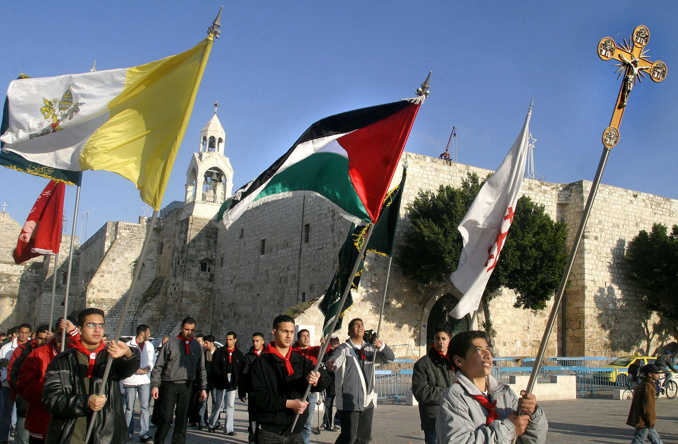 Palestinian Catholic boy scouts march with their national flag and the Vatican's flag during a procession for Pope John Paul II outside the Church of the Nativity in Bethlehem, April 2, 2005. (AFP)