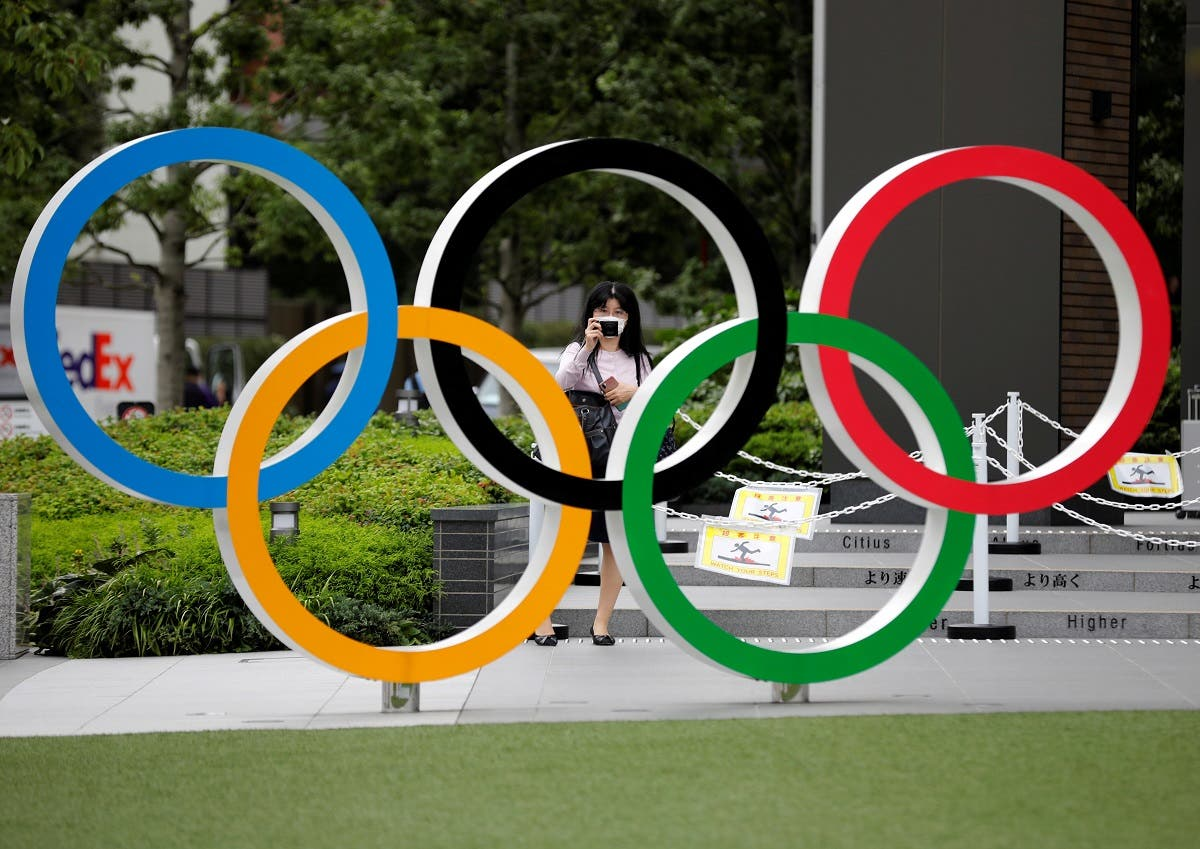 A woman wearing a protective mask amid the coronavirus disease (COVID-19) outbreak, takes a picture of the Olympic rings in front of the National Stadium in Tokyo, Japan October 14, 2020.