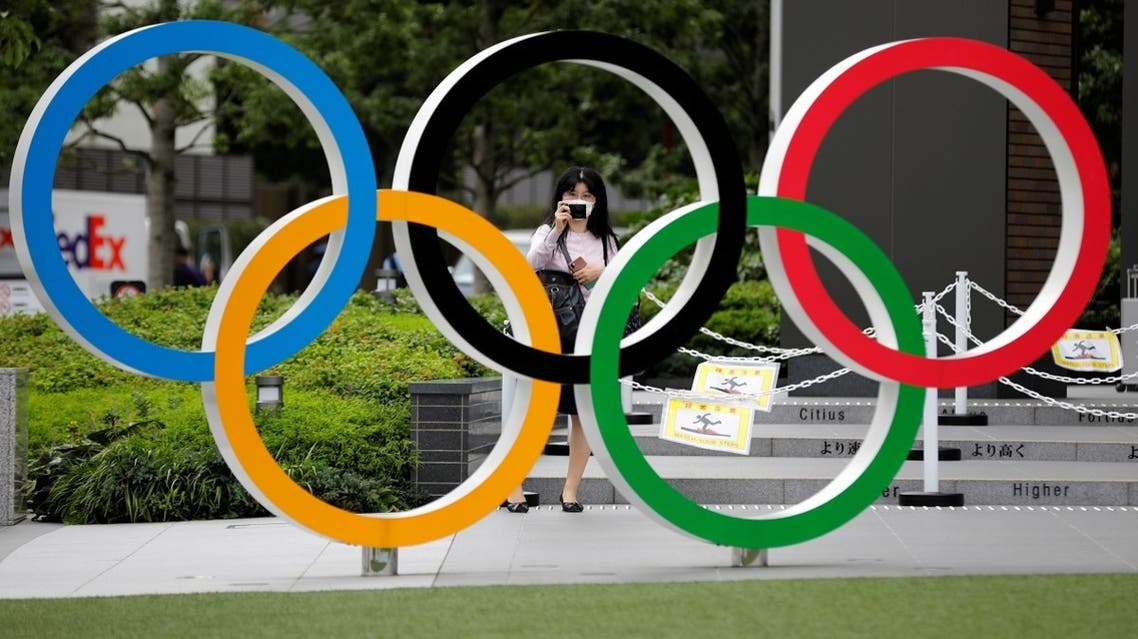 A woman wearing a protective mask amid the coronavirus disease (COVID-19) outbreak, takes a picture of the Olympic rings in front of the National Stadium in Tokyo, Japan October 14, 2020. REUTERS