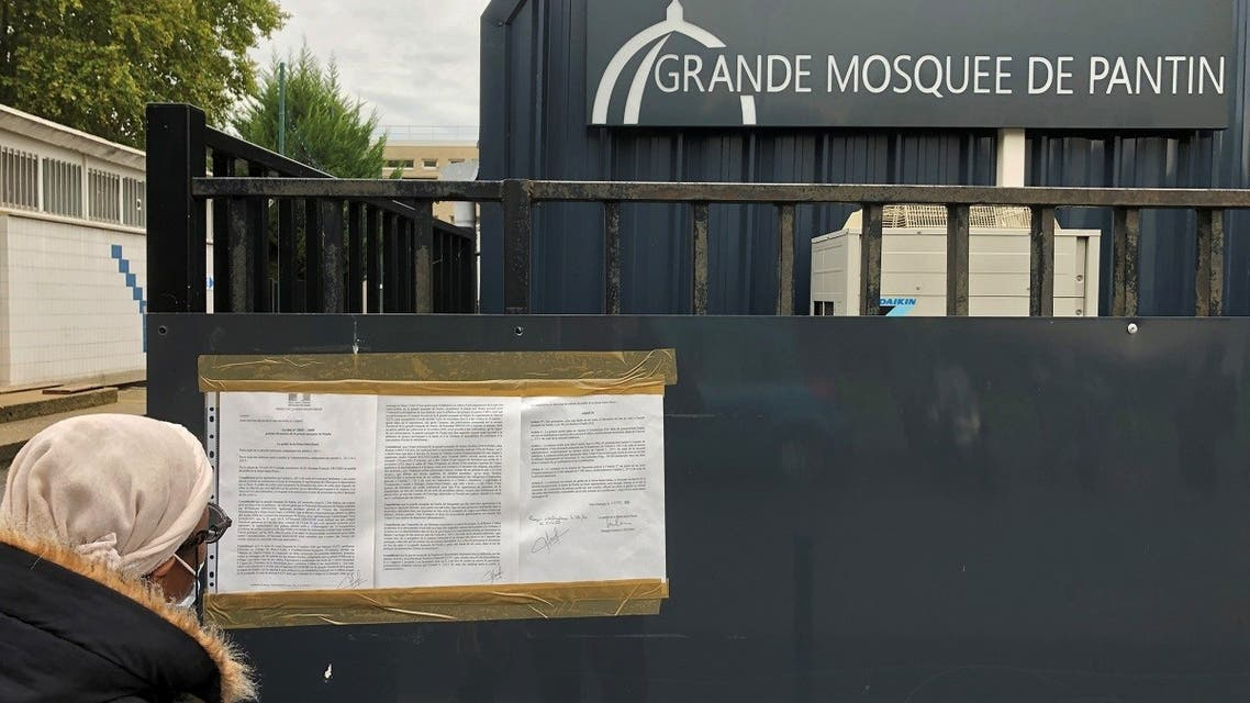 A woman reads a prefectoral decree installed on the entrance gates of the Grand Mosque of Pantin, near Paris, France, October 20, 2020. (Reuters)