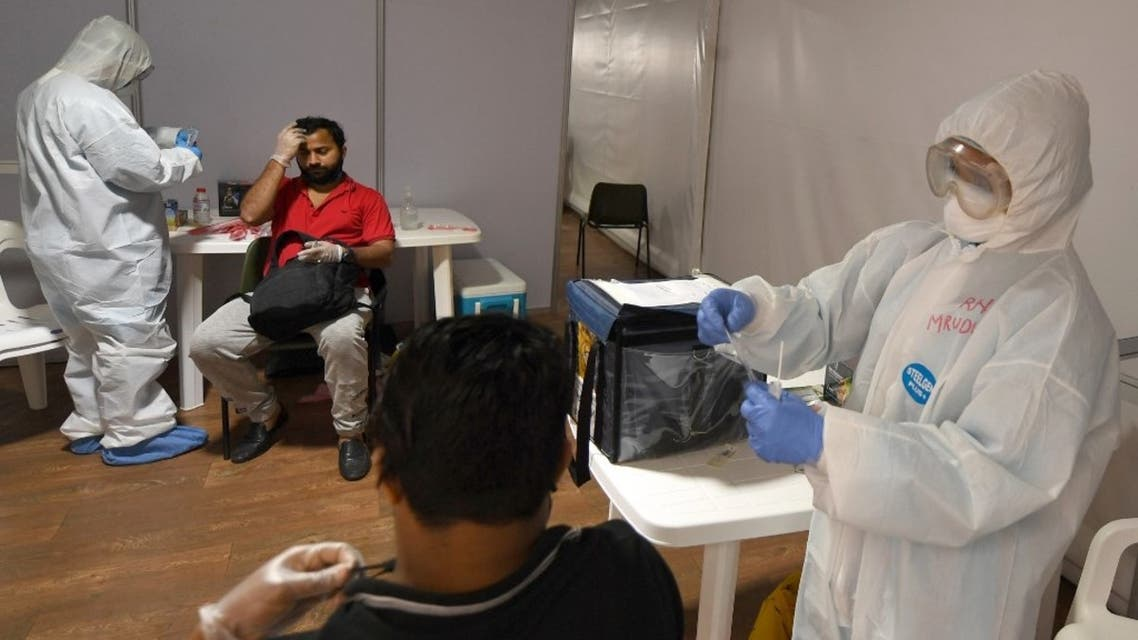 Foreign workers get tested for the novel coronavirus at a testing centre in the Naif area of the Gulf Emirate of Dubai, on April 15, 2020. (AFP)
