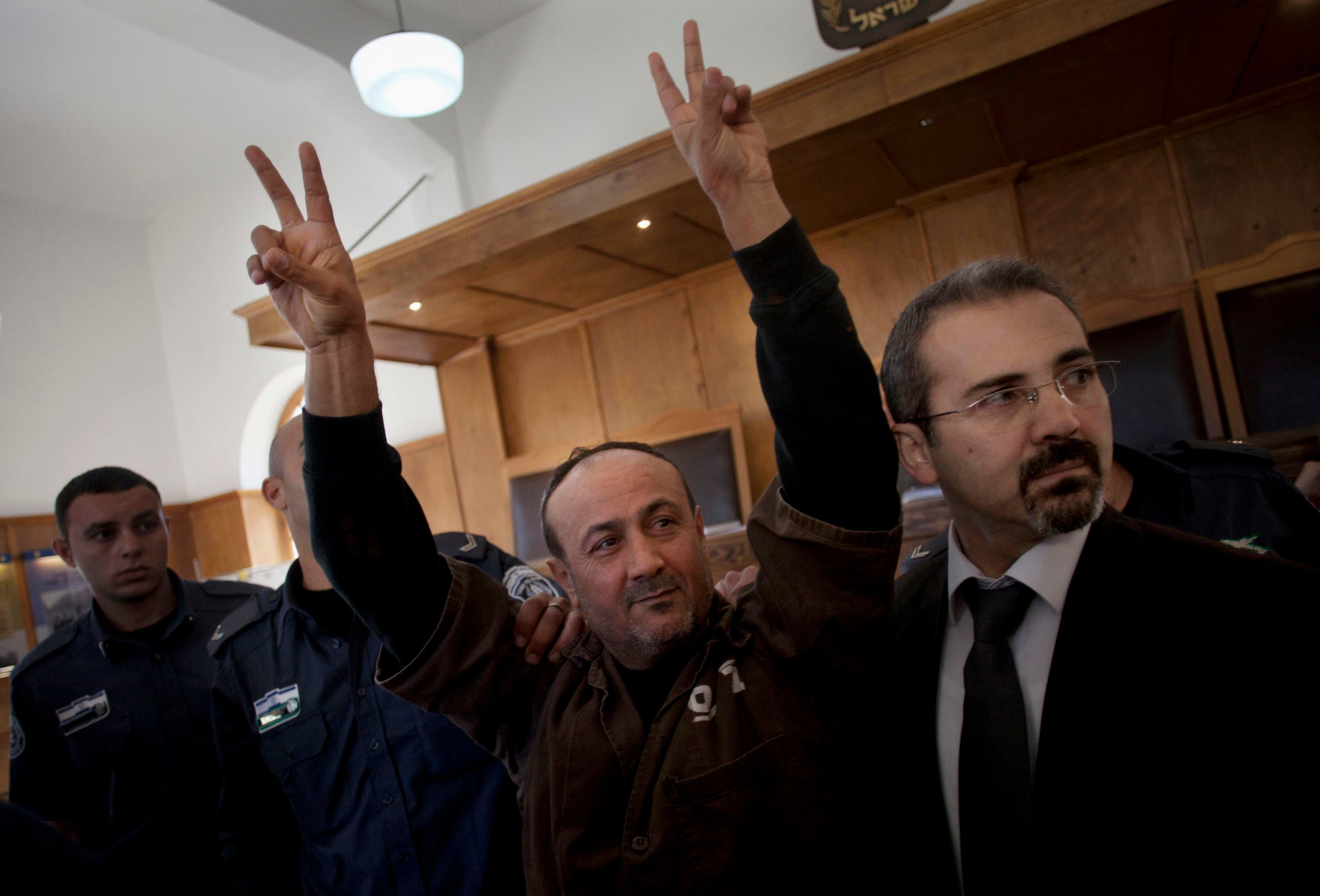 Senior Fatah leader Marwan Barghouti makes the victory sign in front of the media during his arrival to testify in a trial at a Jerusalem court on Jan. 25, 2012. (AP)