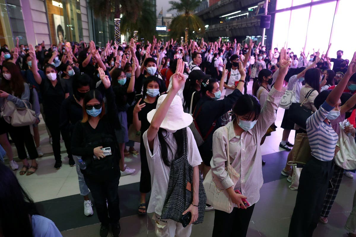 Pro-democracy protesters make a three-finger salute at 6:00 Pm, at the time the national anthem is usually played in all public transport stations in Bangkok, Thailand, on October 20, 2020. (Reuters)