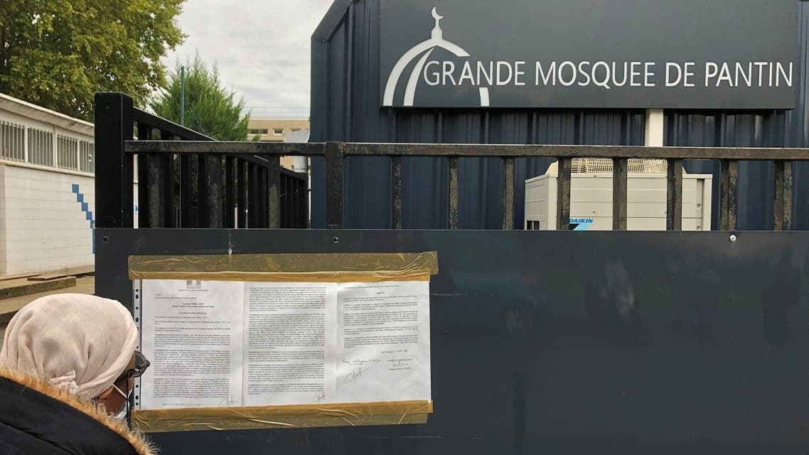 A woman reads a prefectoral decree installed on the entrance gates of the Grand Mosque of Pantin, near Paris, France, on October 20, 2020. (Reuters)