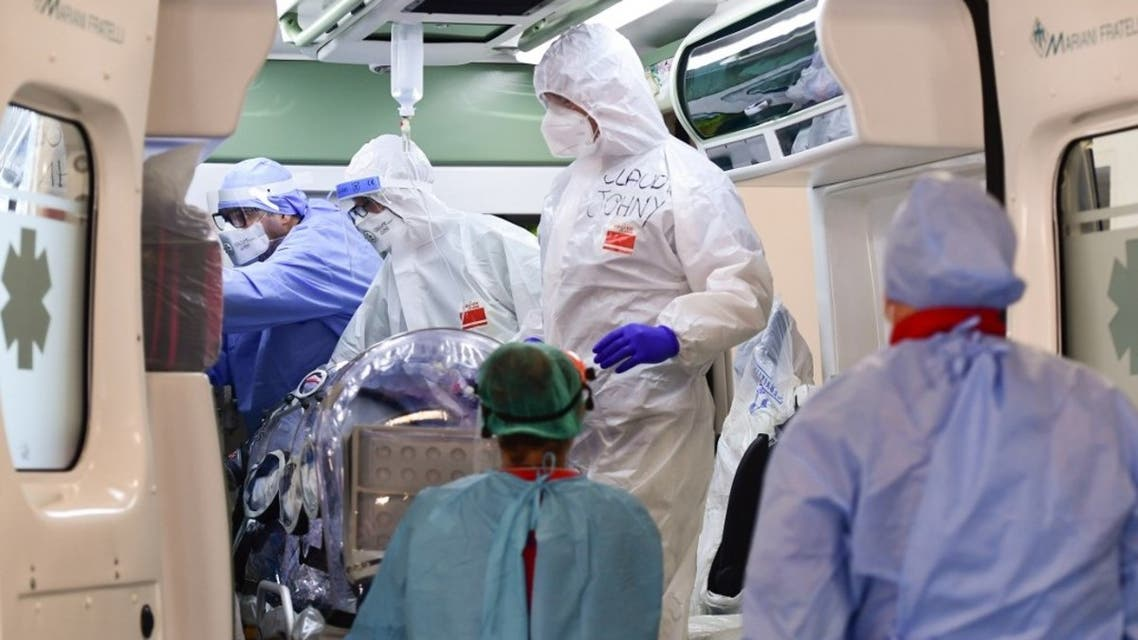 Medical staff transfer from the Garbagnate Milanaise hospital a patient with Covid-19 in a bio-containment stretcher for infectious diseases to Varese hospital near Milan on October 19, 2020. (AFP)