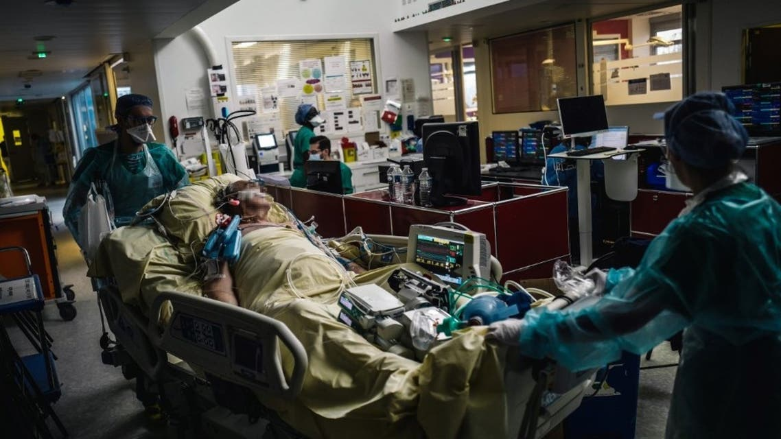 This file photo taken on October 14, 2020 medical staff members transporting a patient at the intensive care unit of the Lariboisiere Hospital of the AP-HP in Paris. (AFP)
