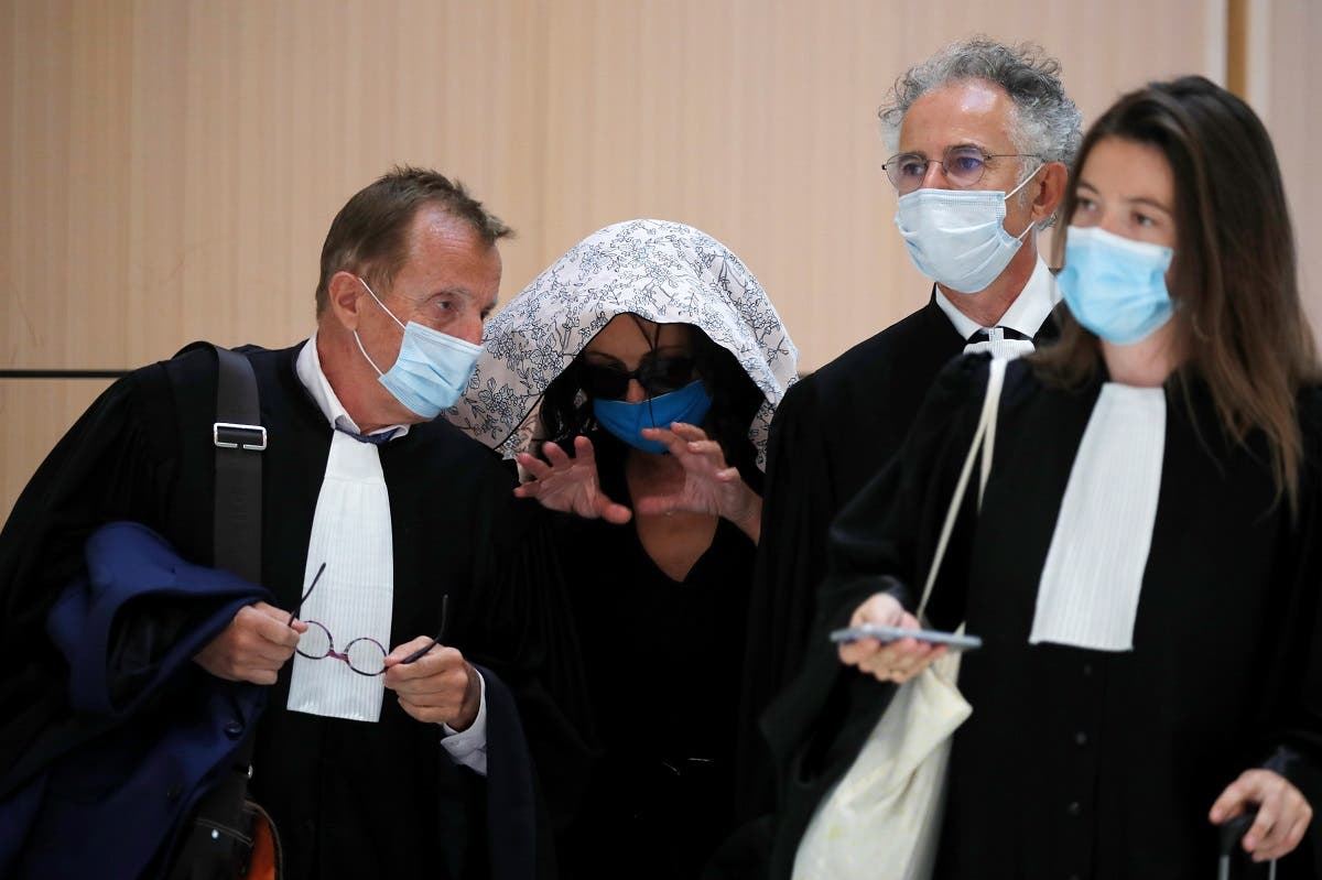 An alleged victim of Swiss academic Tariq Ramadan, hiding her face, gestures as she talks with her lawyers as she arrives to attend Tariq Ramadan's trial at the Paris courthouse, France, September 16, 2020. (Reuters)