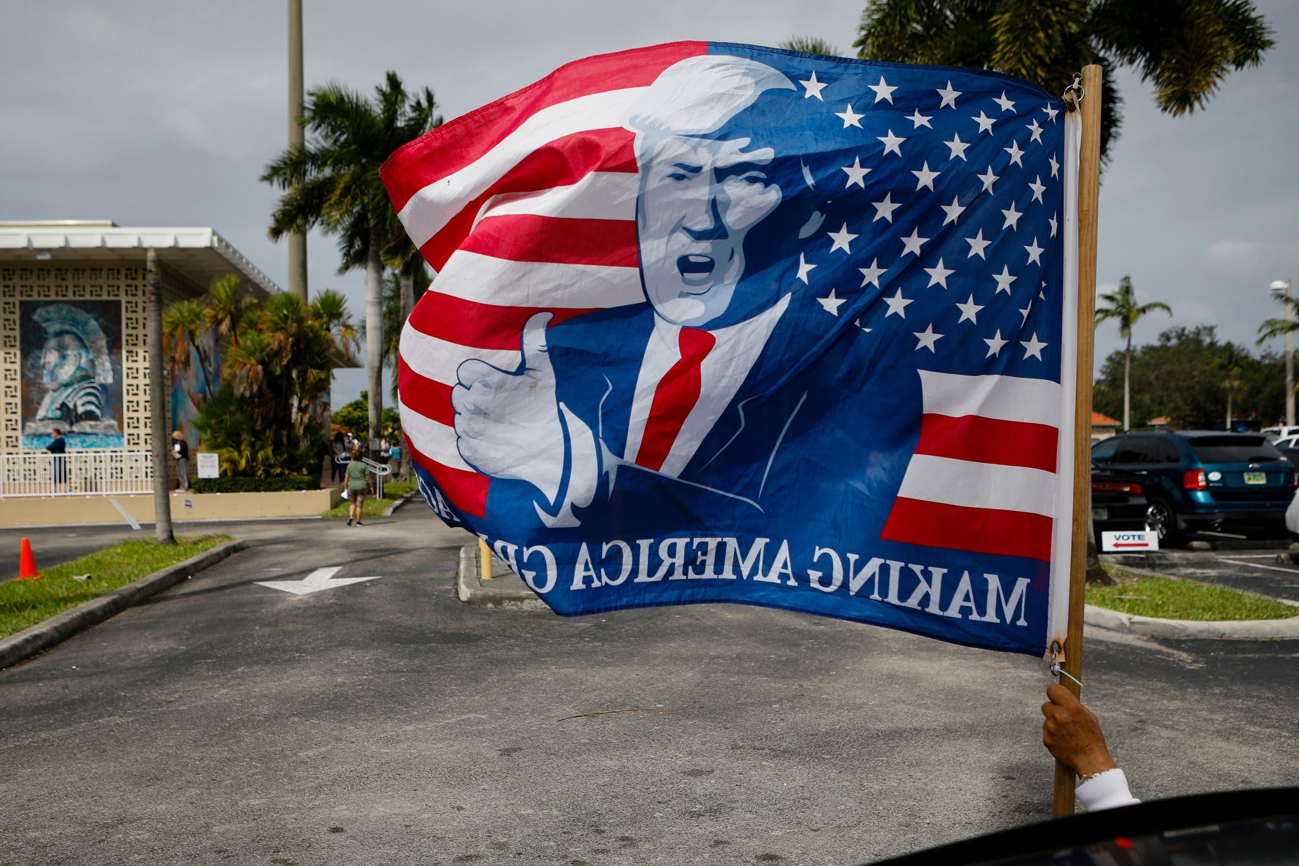 أحد مناصري ترمب يرفع علماً عليه صورة الرئيس في فلوريدا