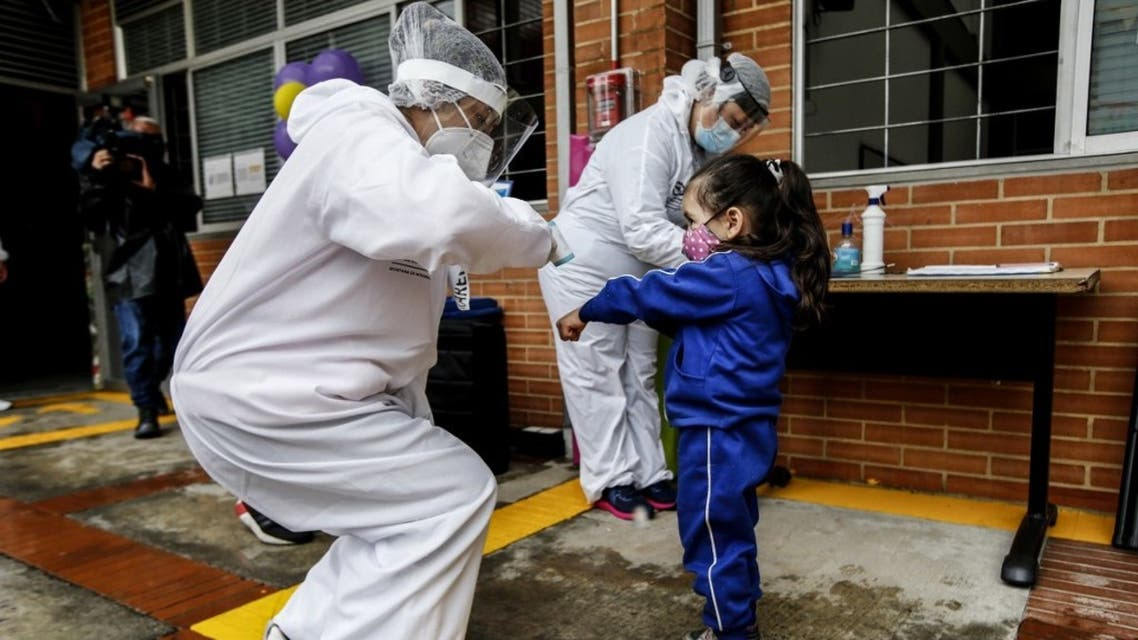 A teacher wearing personal protective equipment checks a child's temperature during the opening of the kindergartens in Bogota, on September 23, 2020 amid the coronavirus pandemic. (AFP)