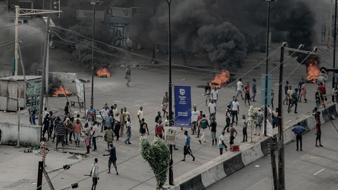 People are seen near burning tires on the street, in Lagos. (Reuters)