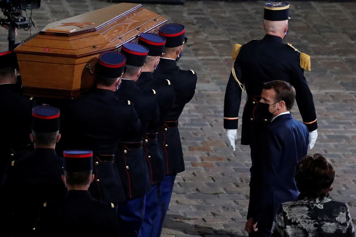 President Macron watches the coffin of slain teacher Samuel Paty being carried in the courtyard of the Sorbonne university during a national memorial event, in Paris, France October 21, 2020. (Francois Mori/Pool via Reuters)