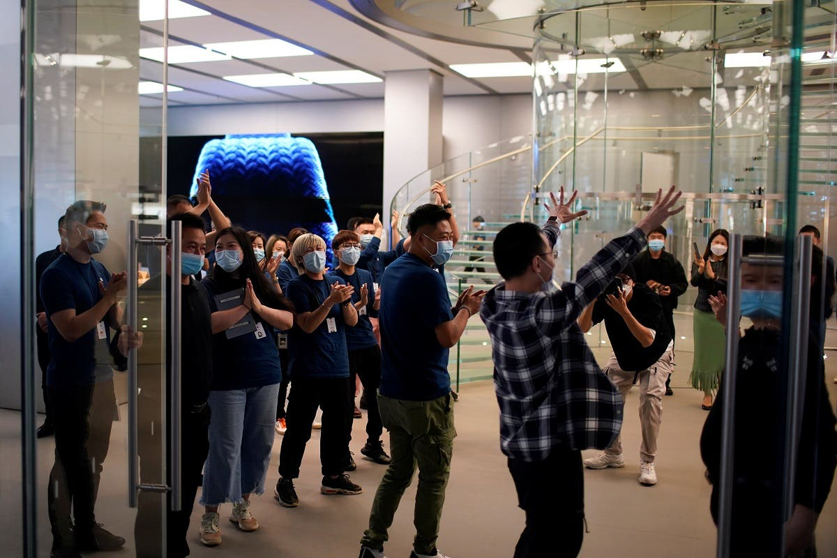 A man reacts while entering at an Apple Store before Apple's 5G new iPhone 12 go on sale, as the coronavirus disease (outbreak continues in Shanghai, China, on October 23, 2020. (Reuters)