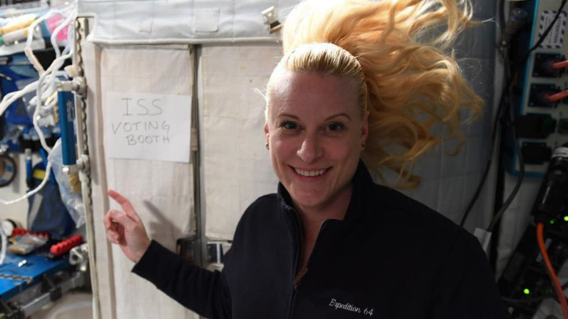 International Space Station (ISS) crew member Kate Rubins pointing to a sign reading ISS voting booth. (AFP)