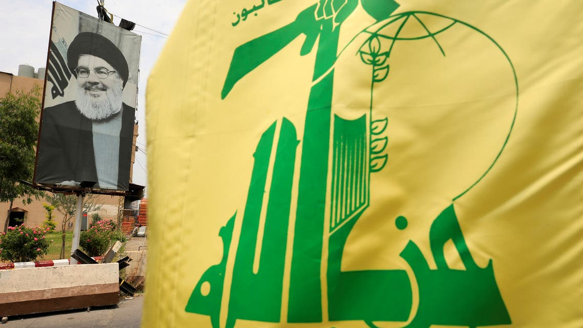 FILE PHOTO: A Hezbollah flag and a poster depicting Lebanon's Hezbollah leader Sayyed Hassan Nasrallah are pictured along a street, near Sidon, Lebanon July 7, 2020. REUTERS/Ali Hashisho/File Photo