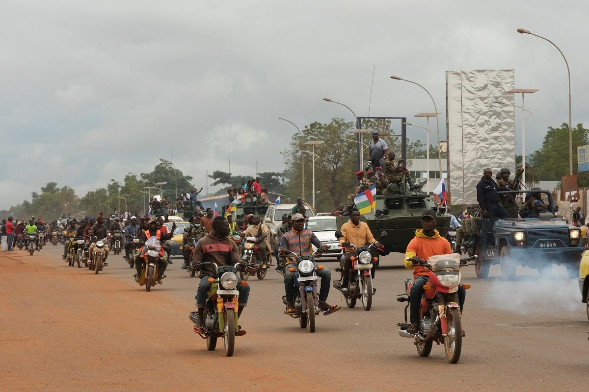 Motorcycle taxi operators ride next to military vehicles that escorts the convoy of Russian armored personnel carriers (APC) delivered to the Central African Republic army in Bangui, October 15, 2020. (AFP)