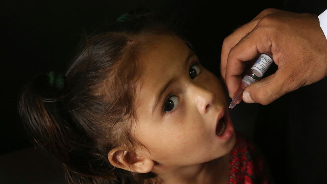 A Pakistani health worker gives a polio vaccine to a girl in a passenger train, in Karachi, Pakistan on May 7, 2018. (AP)
