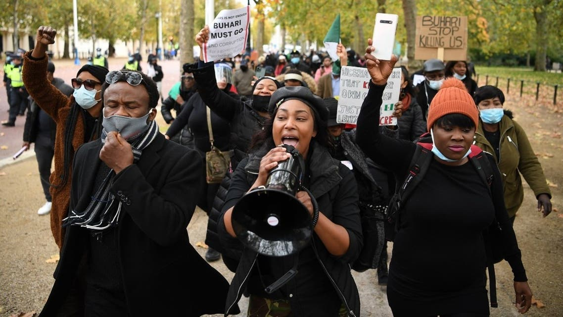 Protestors carry placards and shout slogans against police brutality in Nigeria, as they march along The Mall towards Buckingham Palace in central London on October 24, 2020. (Daniel Leal-Olivas/AFP)