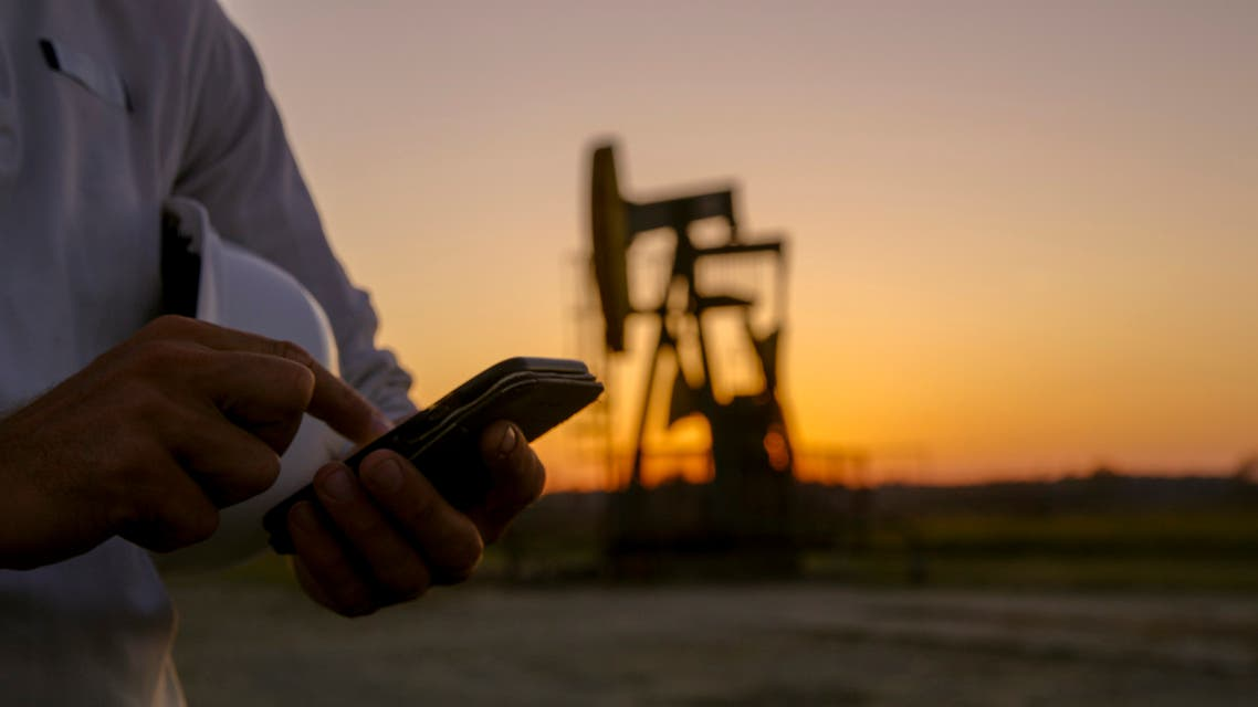 iStock Close up of smart phone against pumpjack