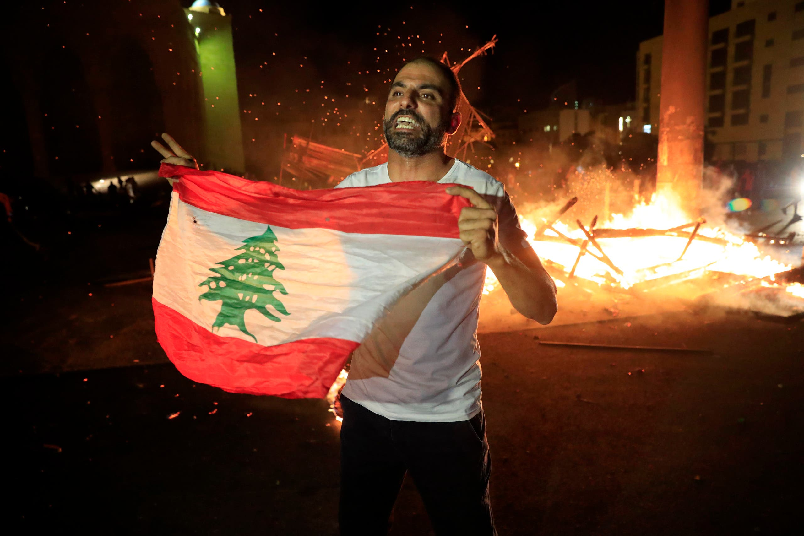 A protester holds the Lebanese flag and shouts slogans denouncing the naming of former Lebanese Prime Minister Saad Hariri as a potential candidate for prime minister, after Hariri's supporters burned a significant protest symbol erected in downtown Beirut on Oct. 21, 2020. (File photo: AP)
