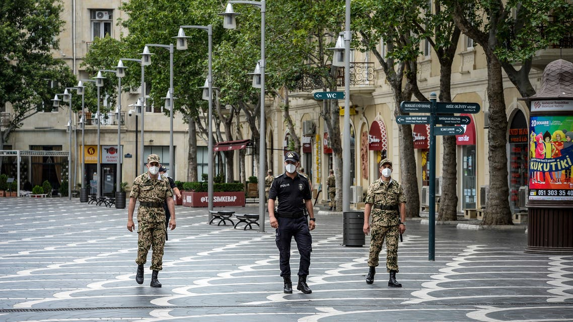 Police officers wearing protective face masks patrol a deserted street in Baku on June 21, 2020, amid the outbreak of COVID-19, caused by the novel coronavirus. Anxiety mingled with anger in Azerbaijan as the Caspian nation reinstated on June 21, 2020 a tight coronavirus lockdown to contain the surge in infections that followed the easing of restrictions weeks ago. Azerbaijanis will now only be allowed to leave home once a day for a maximum of two hours after receiving permission via text message from the authorities, Prime Minister Ali Asadov said in a statement.