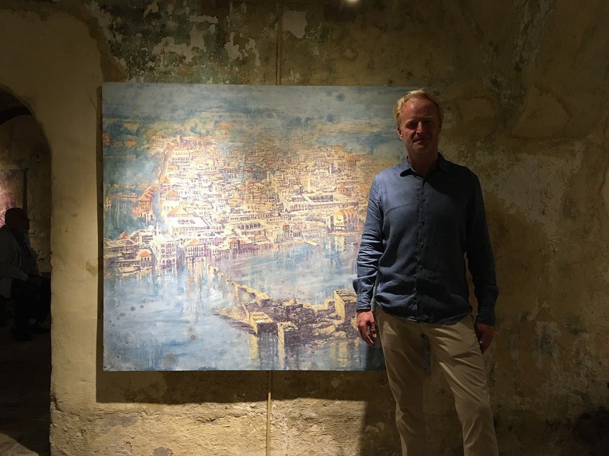 Beirut-based artist Tom Young pictured next to one of his paintings at an exhibition at the Hammam Al-Jadeed. (Robert McKelvey)