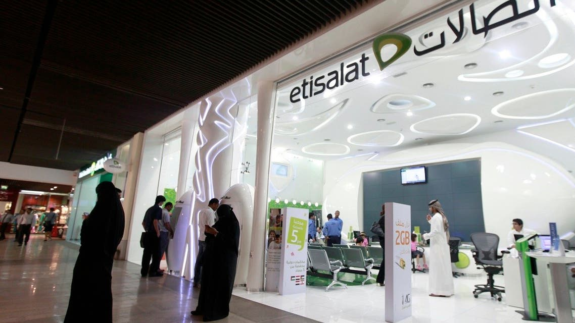 Customers use their mobile phones outside an Etisalat store at a shopping mall in Dubai. (File photo: Reuters)
