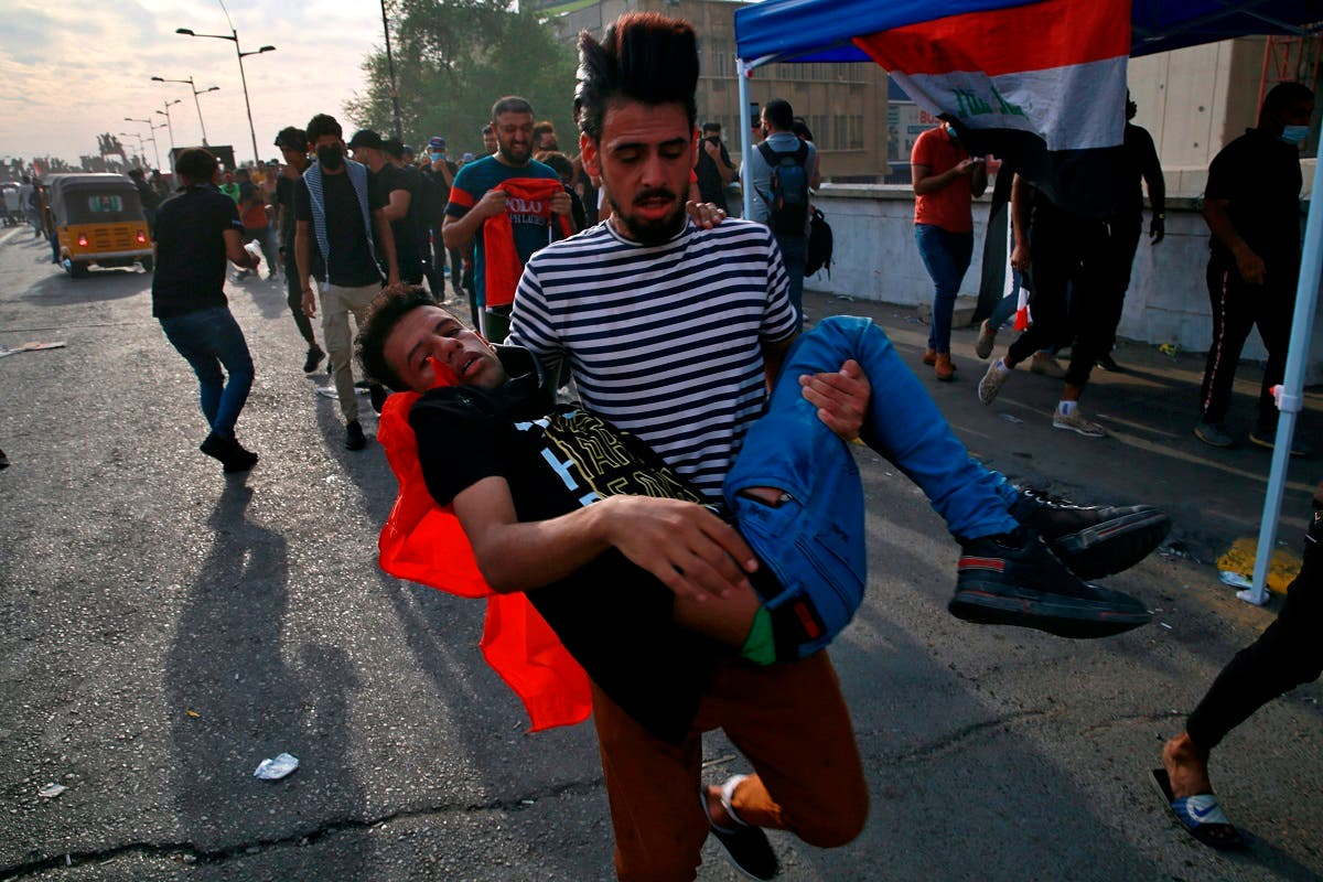 An injured protester is rushed to a hospital during clashes with security forces on the closed Joumhouriya Bridge that leads to the Green Zone government areas, in Baghdad, Iraq, Sunday, Oct. 25, 2020. (AP/Khalid Mohammed)