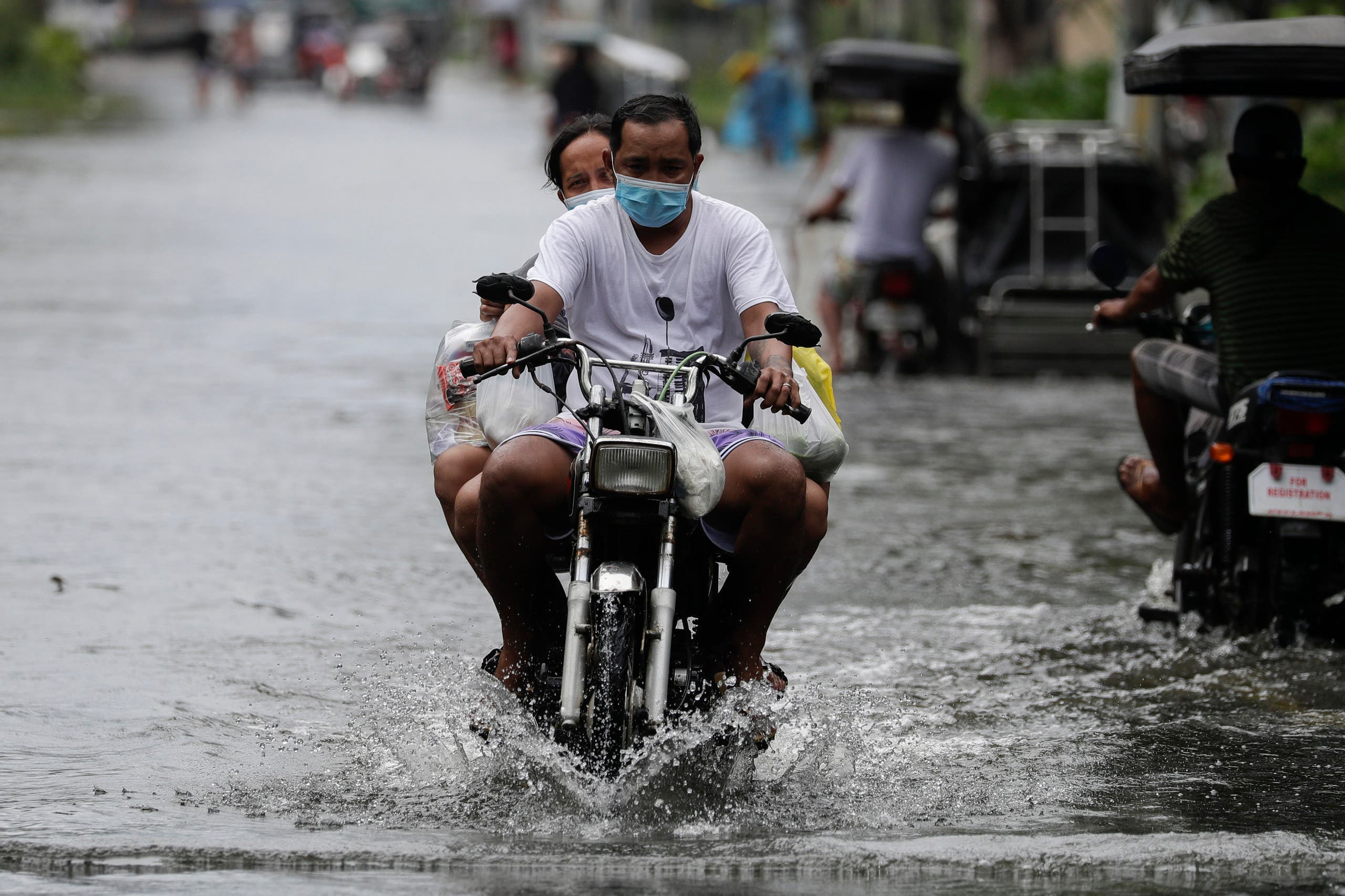 A man driving a bike amid Typhoon Molave in Pampanga province, northern Philippines, Monday, Oct. 26, 2020. (AP)