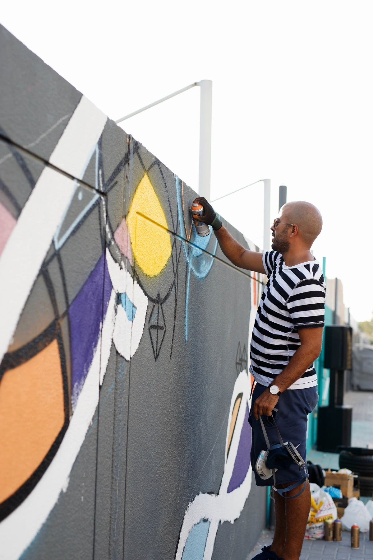 World-renowned artist eL Seed painting a mural  in Alserkal Avenue -- where his studio is based -- that pays tribute to Melehi's work. (Photo by Angelo Jandri, courtesy Alserkal Avenue)