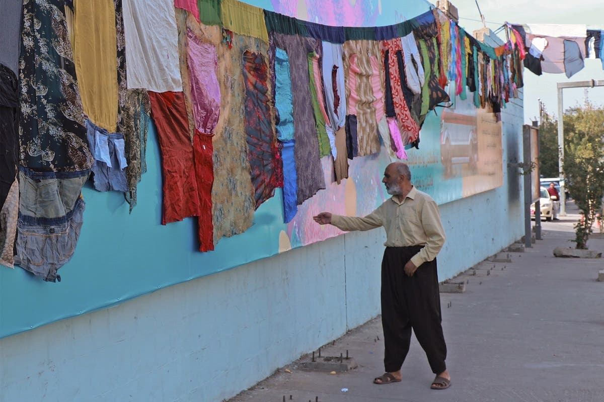 An Iraqi man reaches out to touch an artwork by visual artist Tara Abdallah, in the city of Sulaimaniyah on October 26, 2020. (AFP/Shwan Mohammed)
