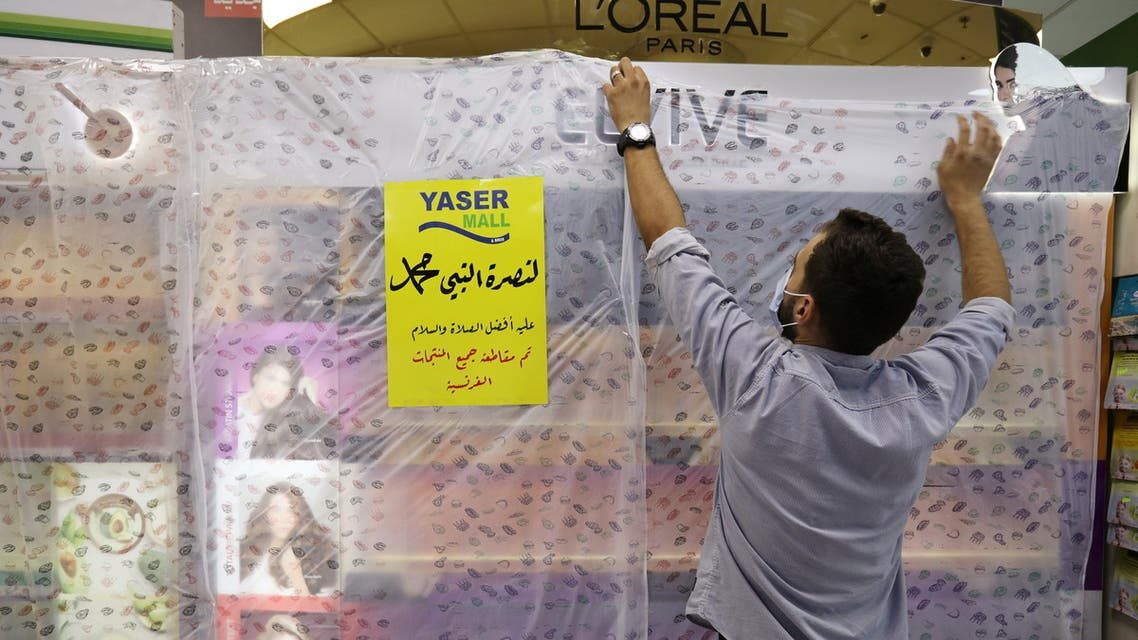 A worker of a mall covers French products in protest against French cartoons of the Prophet Mohammad in Amman, Jordan, October 25, 2020. The cover reads in Arabic In solidarity with the Prophet Mohammad peace be upon him, all French products have been boycotted. (Reuters)