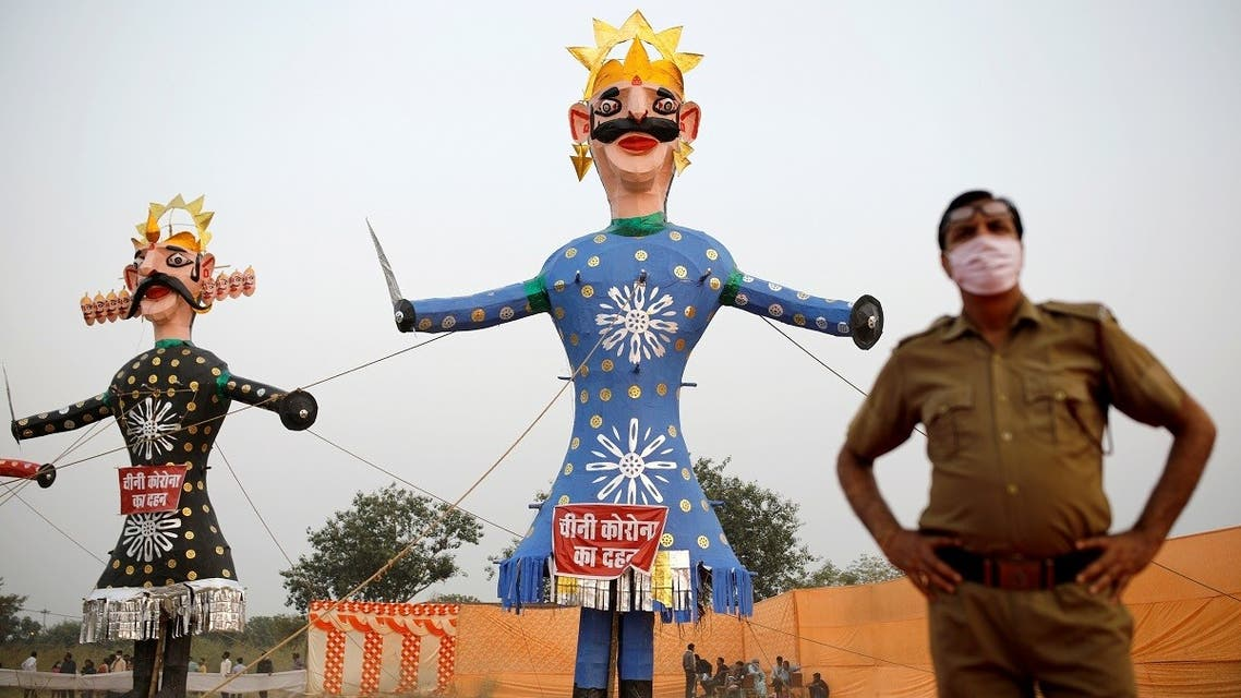 A policeman wearing a protective face mask stands next to the demon King Ravana (L) and his brother Kumbhkarana before they are set on fire during the Hindu festival of Dussehra, amidst the spread of the coronavirus in New Delhi, on October 25, 2020. (Reuters)