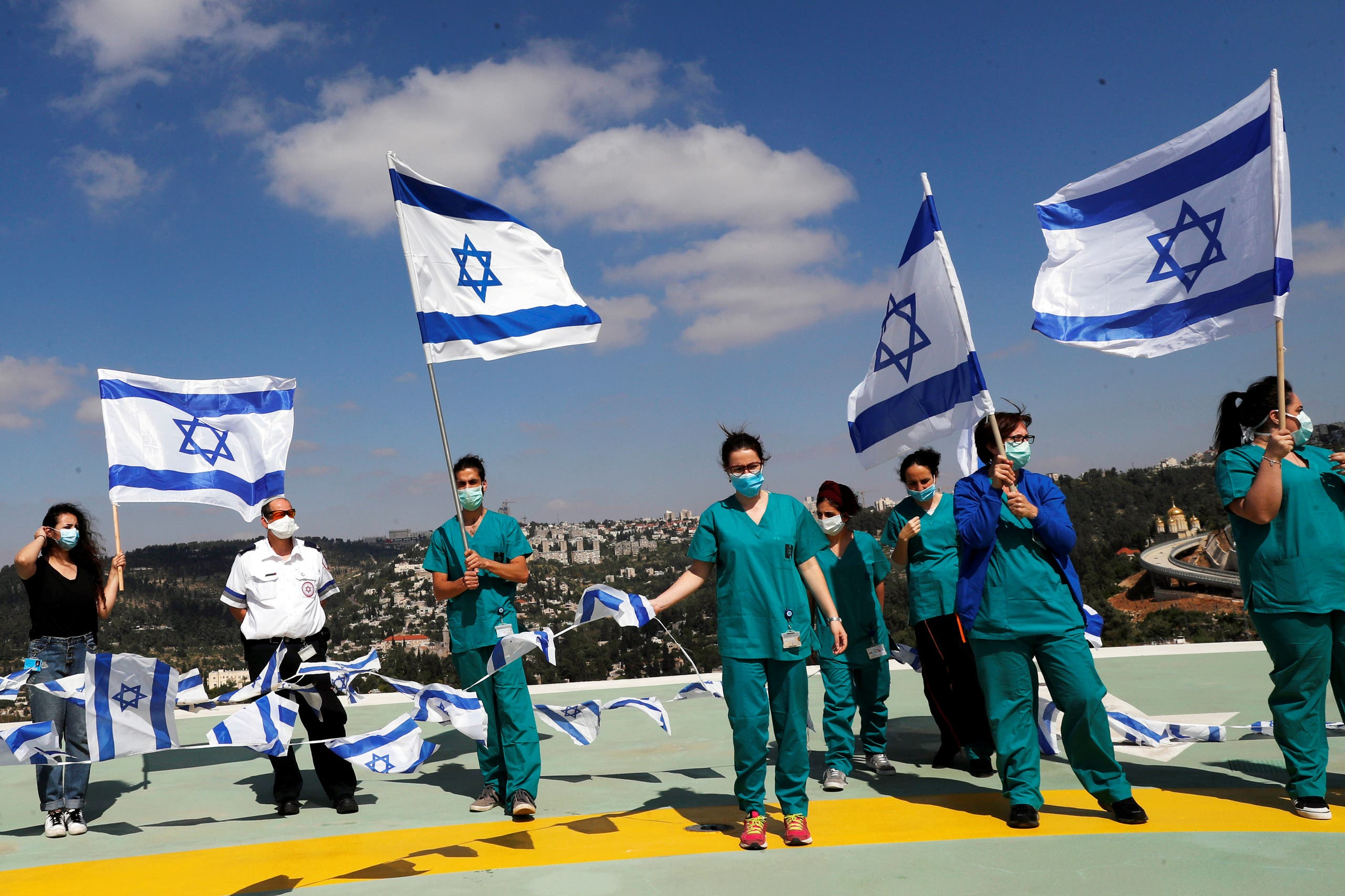 Medical staff hold Israeli national flags before a fly over by the Israeli Air Force over Hadassah Ein Kerem hospital in Jerusalem on April 29, 2020. (Reuters)