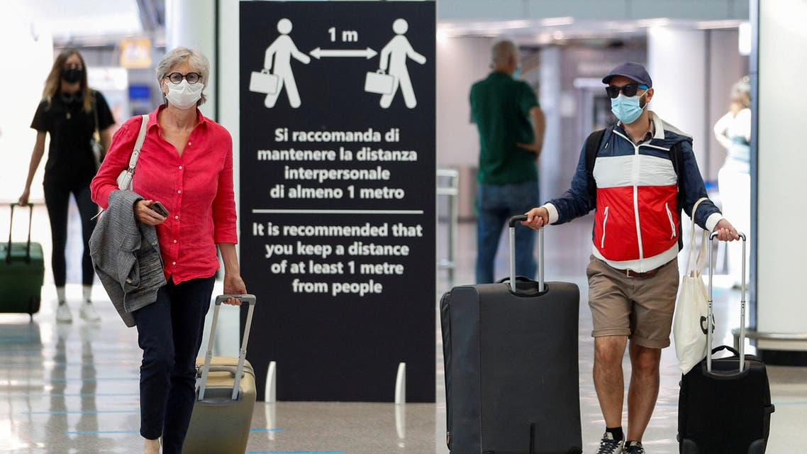 A file photo shows passengers wearing protective face masks walk at Fiumicino Airport in Rome, Italy, June 30, 2020. (Reuters/Guglielmo Mangiapane)
