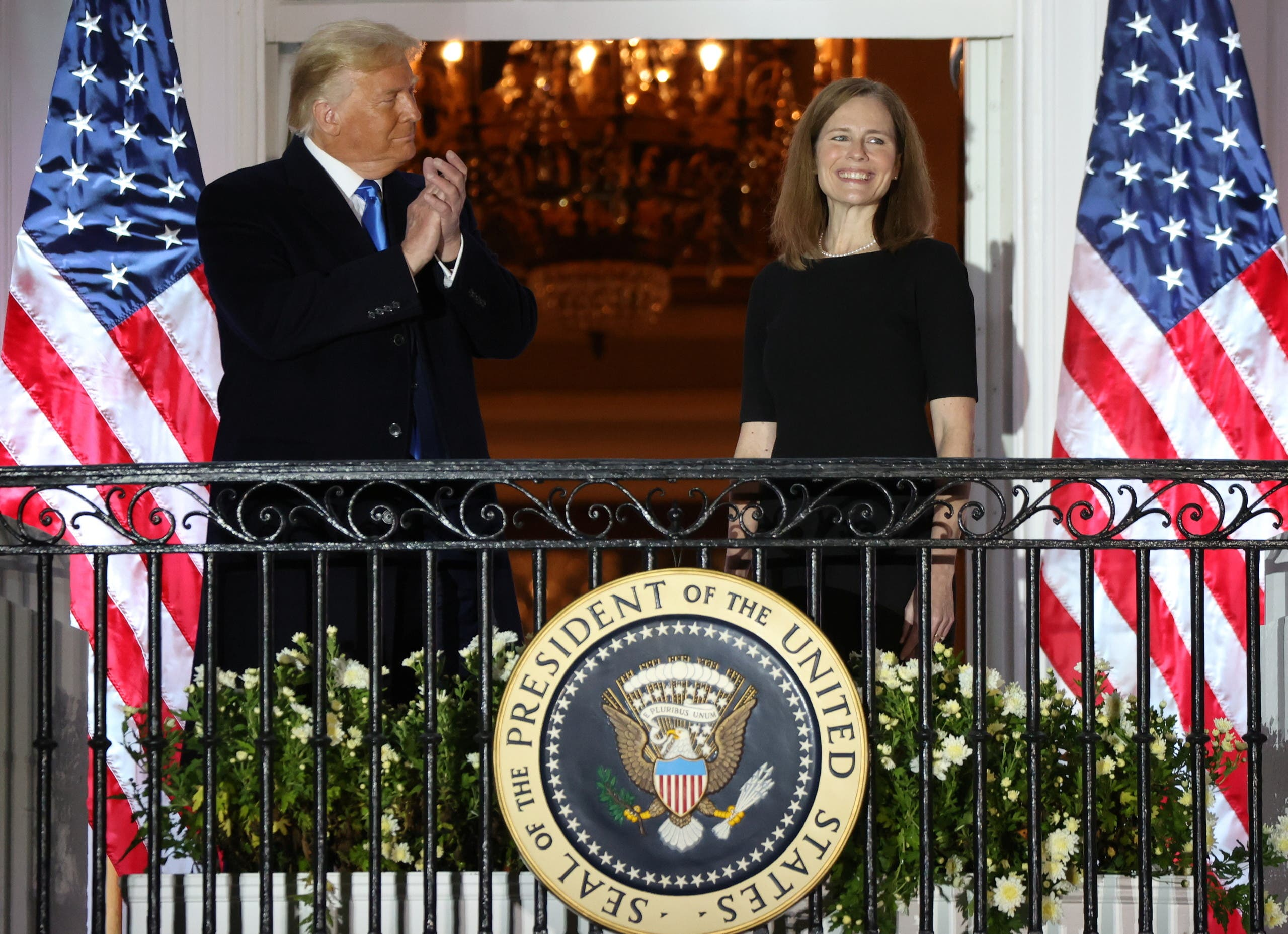 US President Donald Trump applauds US Supreme Court Associate Justice Amy Coney Barrett after she took her oath of office and was sworn in to serve on the court on the South Lawn of the White House in Washington. (Reuters)