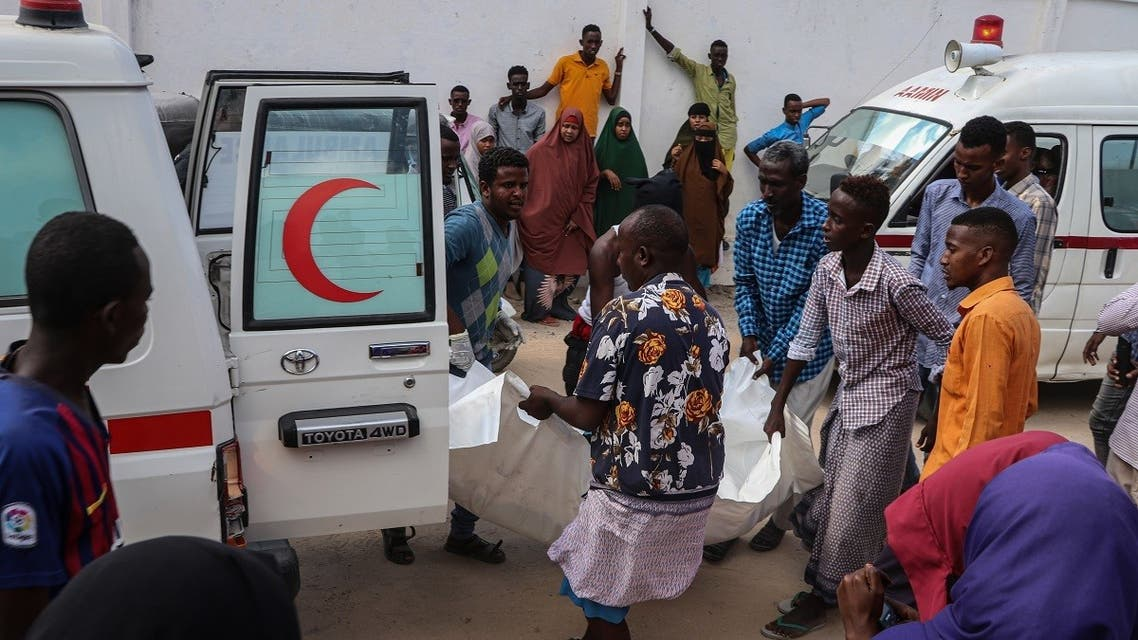 A file photo shows Somali men help to unload a victim, that was injured during a car bombing attack, at the Madina Hospital in Mogadishu, on December 28, 2019. (Abdirazak Hussein Farah/AFP)