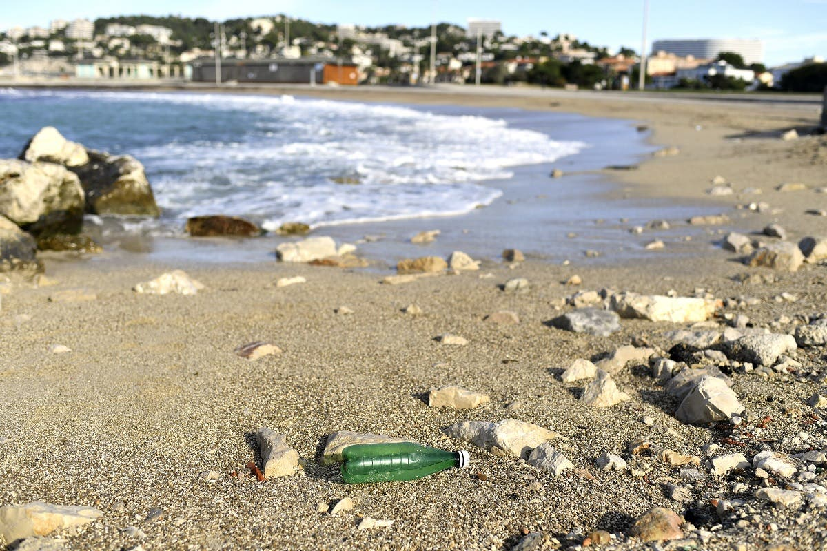 This picture taken in Marseille, southern France, shows a plastic bottle left on the beach by the Mediterranean sea on October 27, 2020. (AFP/Nicolas Tucat)