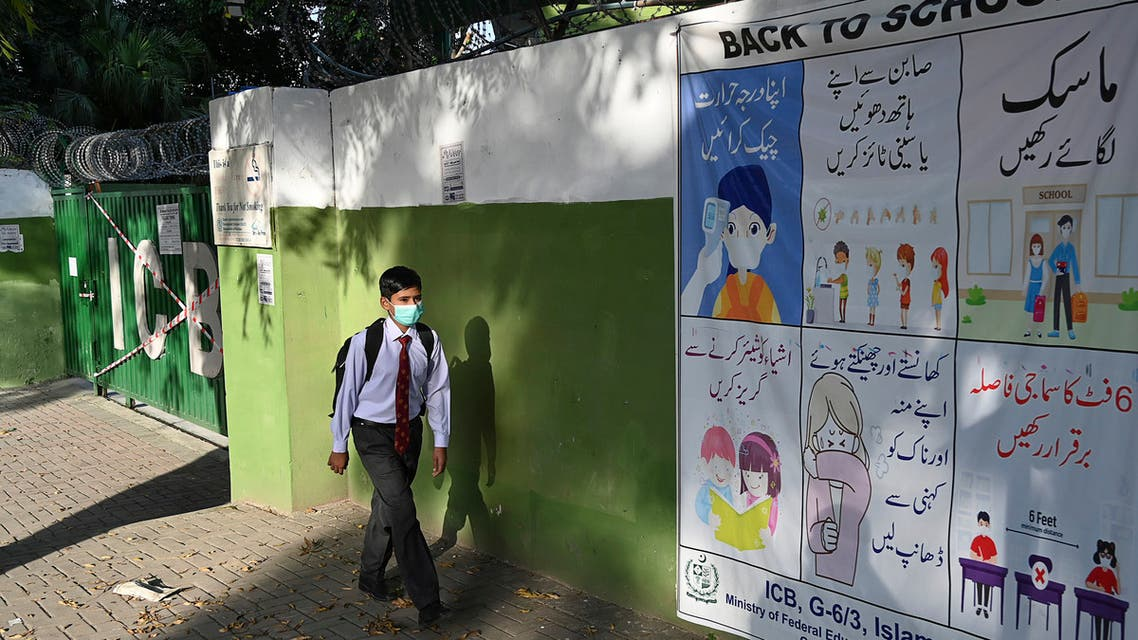 A student wearing a facemask leaves beside a closed school sealed by authorities. (AFP)