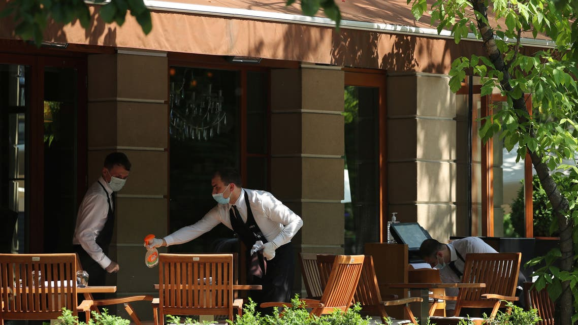 Waiters wearing protective face masks work at a cafe as restaurants and cafes reopen summer terraces in Moscow. (Reuters)
