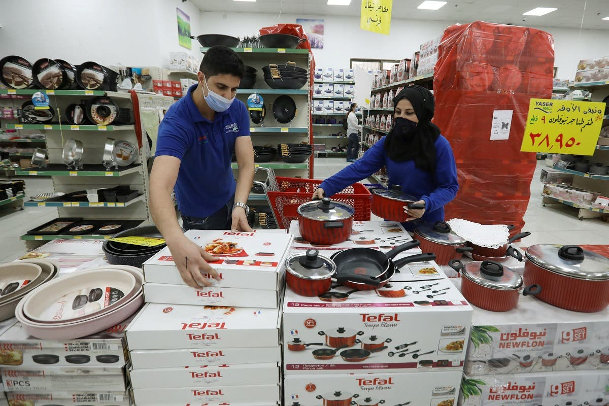 Workers of a mall move displayed French products to a warehouse in protest against French cartoons of the Prophet Mohammad in Amman. (Reuters)