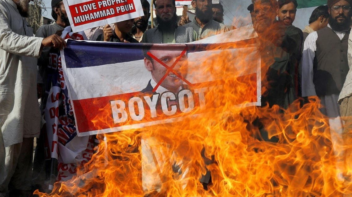 People chant slogans as they set fire to a banner with a crossed-out image of French President Emmanuel Macron during a protest against cartoon publications of Prophet Mohammad in France and Macron's comments, in Karachi, Pakistan. (Reuters)