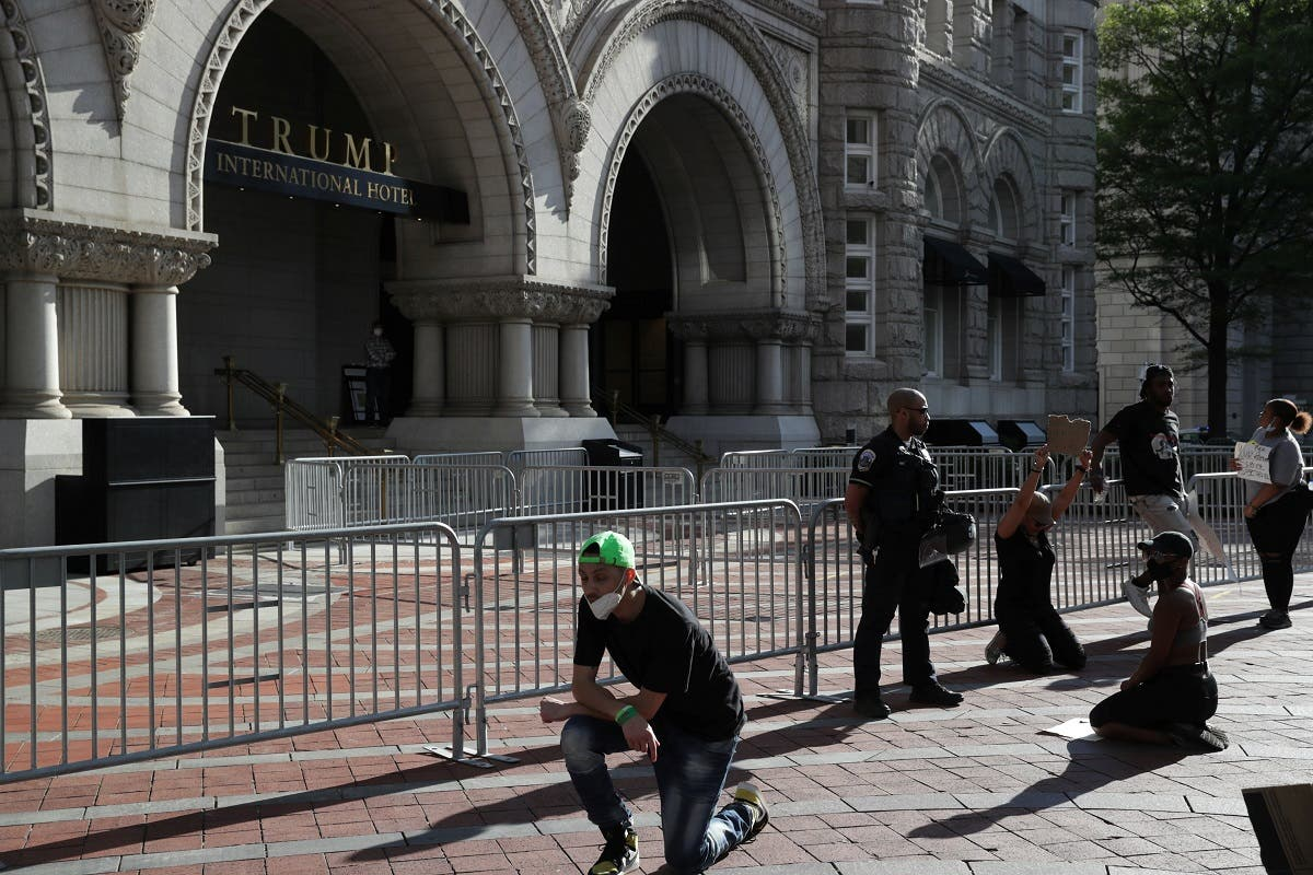 Protesters kneel in front of law enforcement officers at the Trump International Hotel in Washington, DC, May 31, 2020. (Reuters)