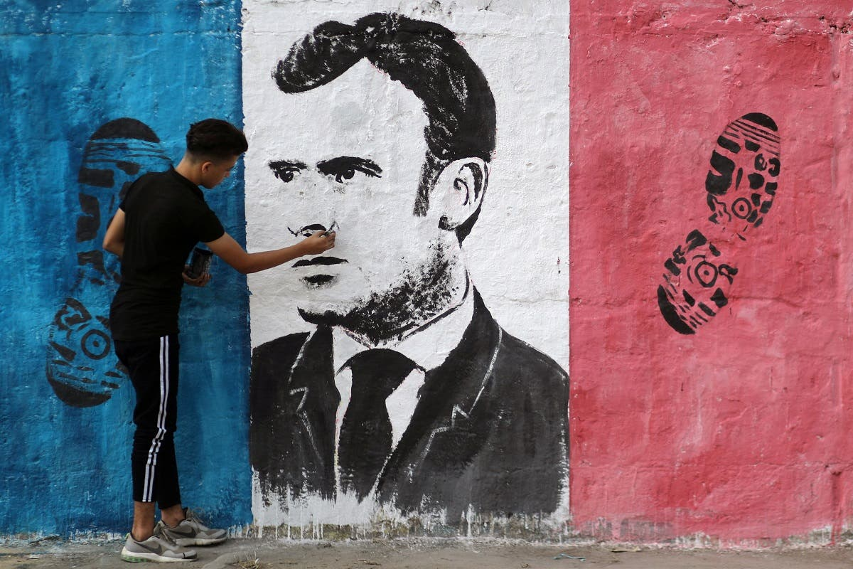 A Palestinian artist paints an anti-French President Emmanuel Macron mural to protest against the publications of a cartoon of Prophet Mohammad in France and Macron's comments, in Gaza City. (Reuters)
